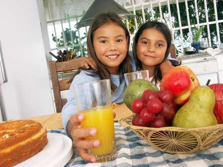 Two little hispanic girls having breakfast in the kitchen
