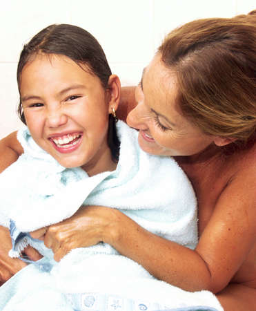 rejuvenated: Hispanic mother drying her daughter with a towel Stock Photo