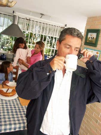 Hispanic man drinking a hot beverage in the kitchen Standard-Bild