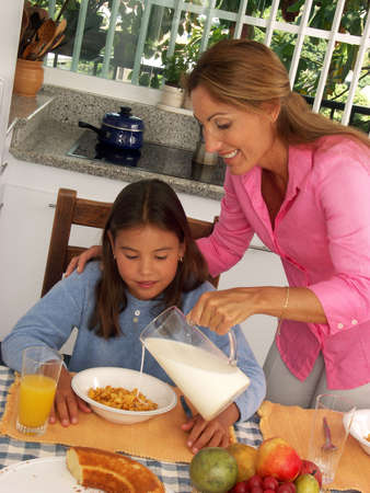 Hispanic woman pouring milk into a bowl of cereal for her daughter Stock Photo - 22525797
