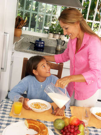 Hispanic woman pouring milk into a bowl of cereal for her daughter Stock Photo - 22525801