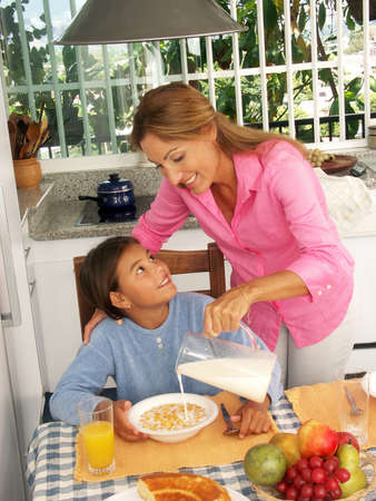 Hispanic woman pouring milk into a bowl of cereal for her daughter Stock Photo - 22525803