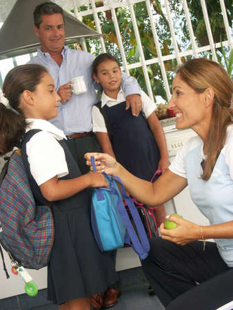 latin kids: Hispanic family getting their kids ready for school