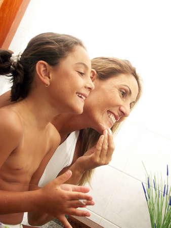 niños latinos: Madre e hija mirando a un espejo en el cuarto de baño