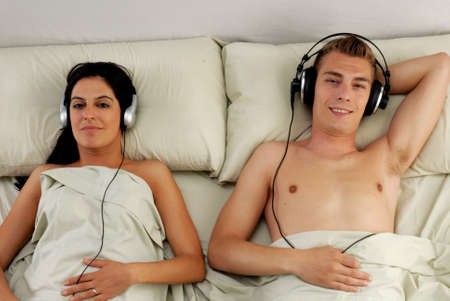 Young couple listening to music using headphones on bed photo