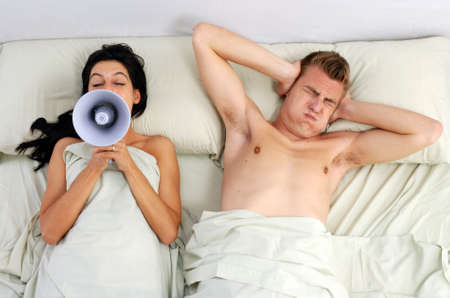 Young woman using a megaphone while young man closing his ears Stock Photo - 22501397