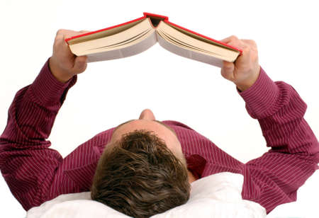 Young man lying down on a bed while reading a book