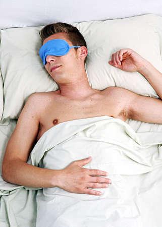 Young man wearing eye mask while sleeping Stock Photo - 22521073