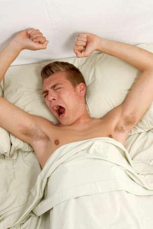 yawing: Hombre joven que estira en la cama