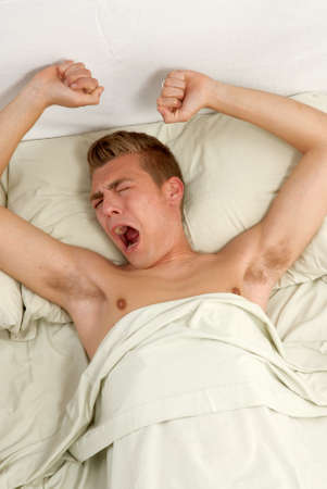 yawing: Young man stretching in bed