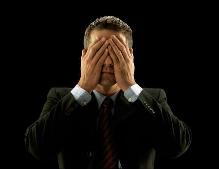 Businessman covering his eyes on black background photo