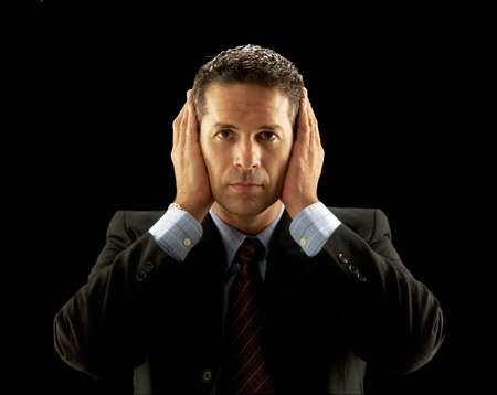 Businessman covering his ears on black background