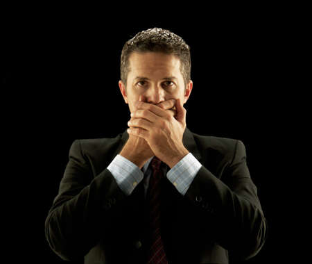 Businessman covering his mouth on black background