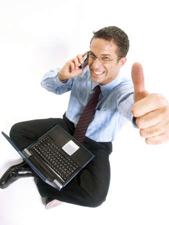 Young businessman sitting down with a laptop and a phone on white background Stock Photo - 22525866