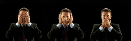 evil eyes: Businessman covering his mouth, eyes and ears on black background Stock Photo