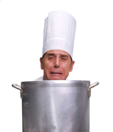 Cook looking upset behind a large pot on white background Stock Photo
