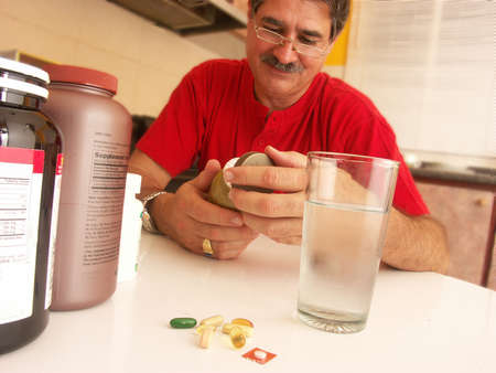 Hispanic man with pills and supplements