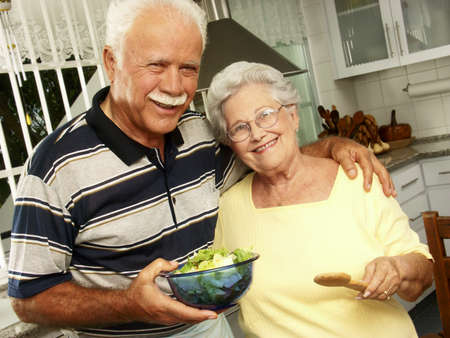 An elderly couple making salad in the kitchen Stock Photo - 22542493