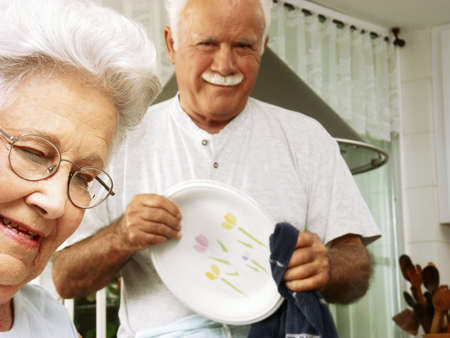 An elderly couple preparing food in the kitchen Stock Photo - 22542516