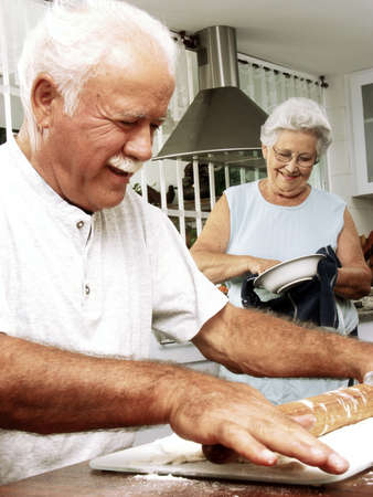 An elderly couple preparing food in the kitchen Stock Photo - 22542518