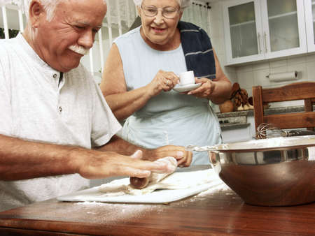 An elderly couple preparing food in the kitchen photo