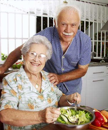 An elderly couple making salad in the kitchen Stock Photo - 22542521