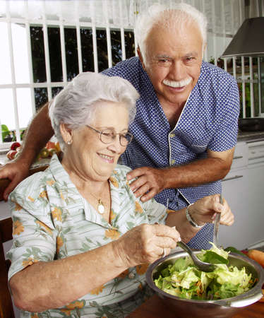 An elderly couple making salad in the kitchen Stock Photo - 22542522