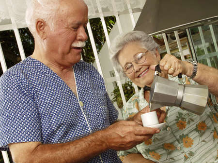An elderly couple having breakfast in the kitchen photo