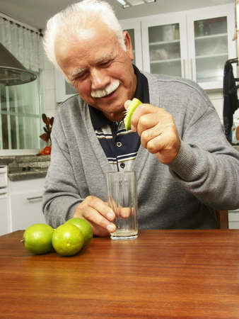 An elderly man squeezing lime juice into a glass photo