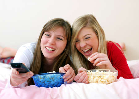 Two young women eating popcorn on the bed while watching tv