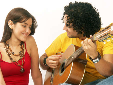 A young couple enjoying each others company with a guitar photo