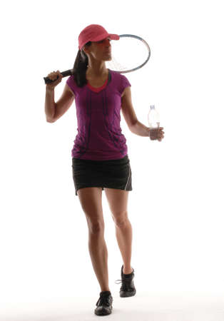 Young woman in gym attire holding a plastic water bottle and tennis racket on white background photo