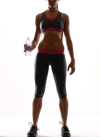 Young woman in gym attire holding a plastic water bottle on white background photo