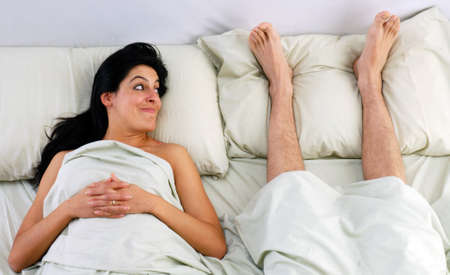 Young woman lying down on bed with husband s foot beside her photo