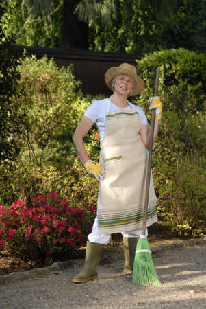 Elderly woman holding a broom in the garden Stock Photo - 22597795