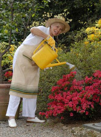 Elderly woman watering the plants