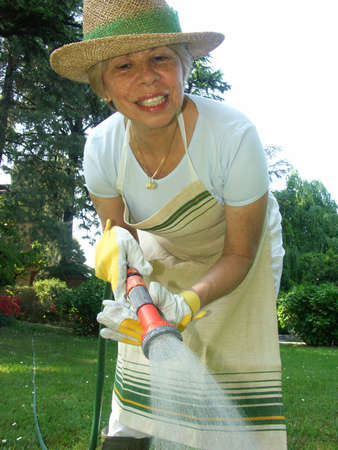 Elderly woman watering the plants Stock Photo - 22597894