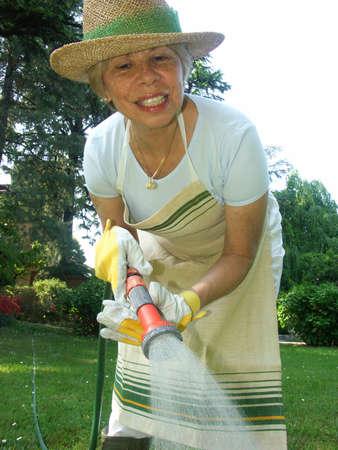 Elderly woman watering the plants Stock Photo - 22597894