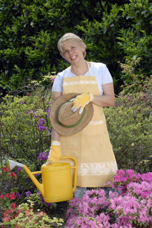 Elderly woman holding a watering can Stock Photo - 22597756
