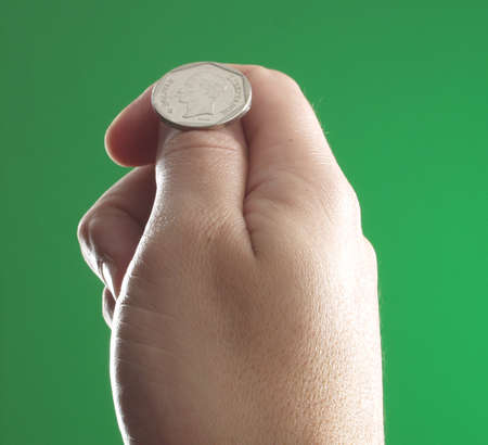 Human hand holding a coin on green background photo