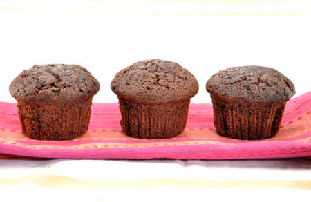 neatly: Chocolate muffins arranged neatly on a table