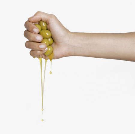 Human hand squeezing olives  Standard-Bild
