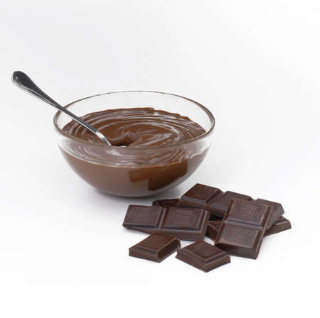 Chocolate bars and chocolate sauce in a bowl on white background