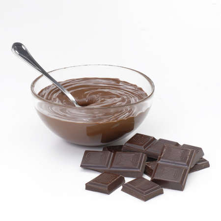 Chocolate bars with chocolate sauce in a bowl on white background
