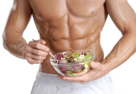 Muscular body holding a bowl of salad on white background Stock Photo
