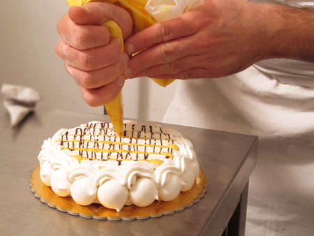 Chef hands preparing cream cake.