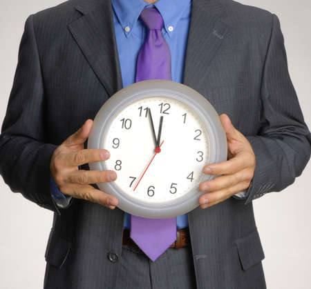 tardiness: Man in suit holding clock up