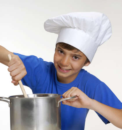 Young boy stirring with a wooden spoon while holding a pot