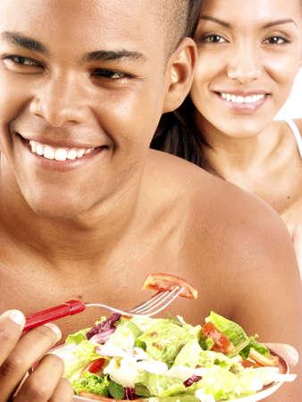 frolicking: Young Hispanic couple enjoying vegetable salad Stock Photo
