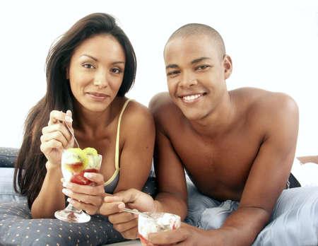 frolicking: Young Hispanic couple frolicking on mattress